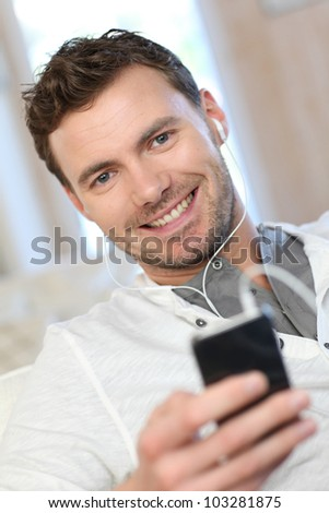 Smiling man using cellphone at home