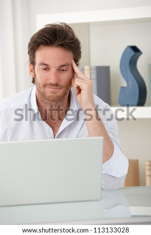 Smiling man using laptop computer at home, sitting at table in living room, looking at screen.