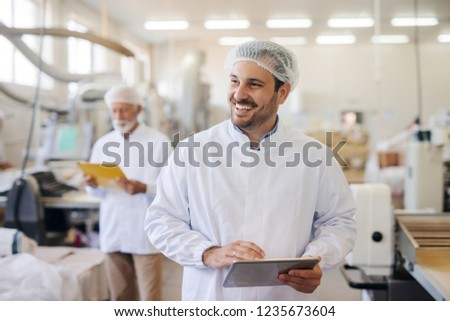 Smiling man using tablet while standing in food factory. #1235673604