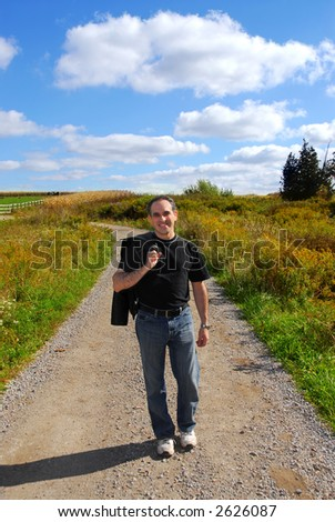 Smiling man walking on a country road