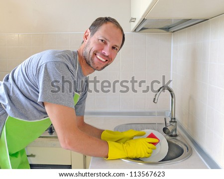 Smiling man washing dish in the kitchen