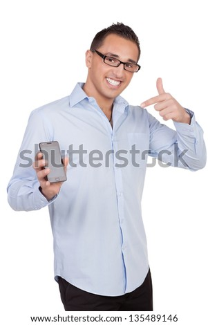 Smiling man wearing glasses showing of his mobile phone by pointing to it while standing looking at the camera isolated on white