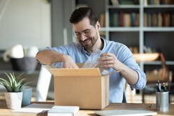 Smiling man wearing glasses unpacking awaited parcel, looking inside, sitting at work desk, satisfied happy customer opening cardboard box with online store order, good shipping delivery service