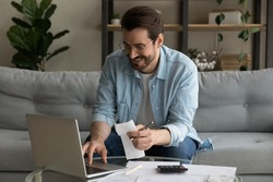 Smiling man wearing glasses using laptop, calculating domestic bills, planning, managing budget, sitting on couch at home, happy businessman browsing online banking service, satisfied by money refund