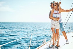 Smiling man with girl in love on a sail boat in the summer
