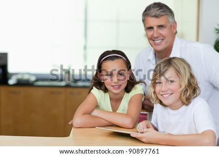 Smiling man with his children and tablet in the kitchen