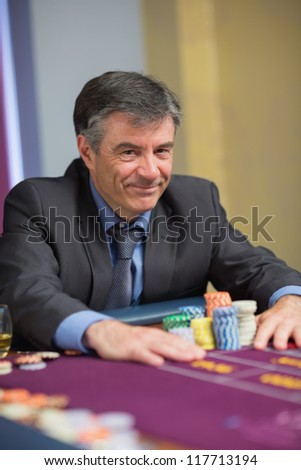 Smiling man with his chips at roulette table