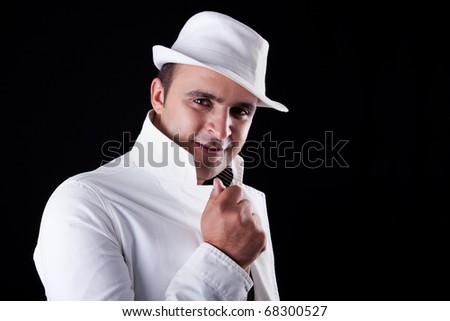 smiling man with his white hat and coat, isolated on black. Studio shot