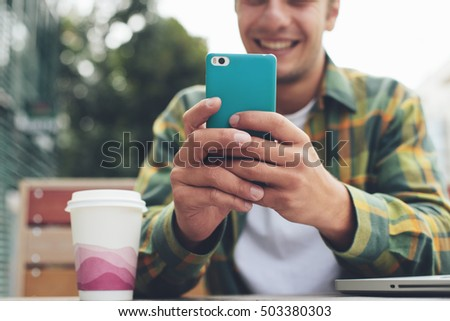 Smiling man with smartphone in hand sitting in street cafe, texting in messenger #503380303