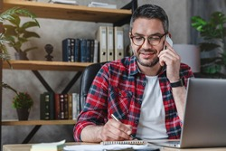 Smiling man writing notes while making phone call and using laptop at home