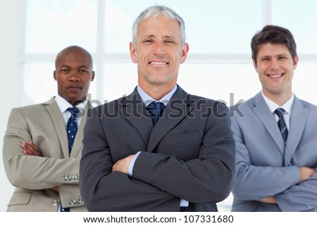 Smiling manager crossing his arms and followed by two young employees in suits