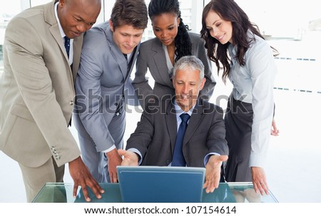 Smiling manager sitting at the desk surrounded by his earnest business team