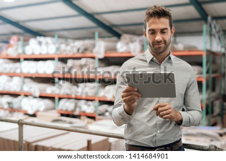 Smiling manager using a digital tablet while standing in a carpet warehouse with stock piled on shelves in the background
