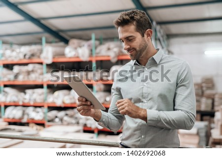Smiling manager using a digital tablet while standing in a warehouse with stacks of carpets and textiles on shelves in the background