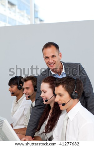 Smiling manager working with his team in a call center