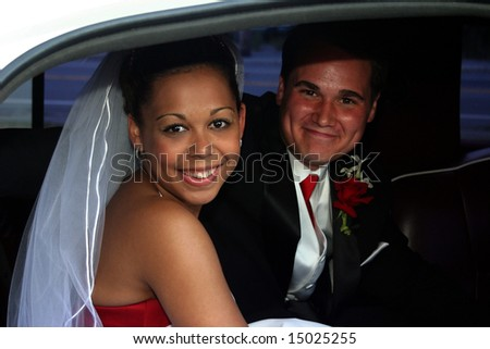 smiling married bi-racial couple in limousine