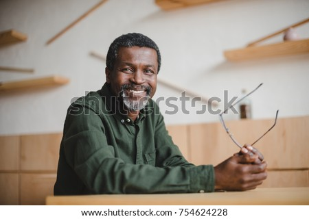 smiling mature african american man sitting in cafe and looking at camera