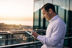 Smiling mature businessman working online with a digital tablet while standing outside on an office building balcony overlooking the city at dusk