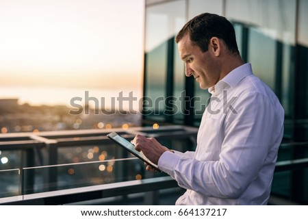 Smiling mature businessman working online with a digital tablet while standing outside on an office building balcony overlooking the city at dusk #664137217