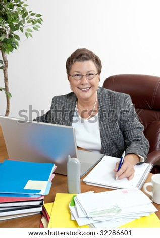 Smiling mature businesswoman at her office desk with phone, laptop computer, etc.