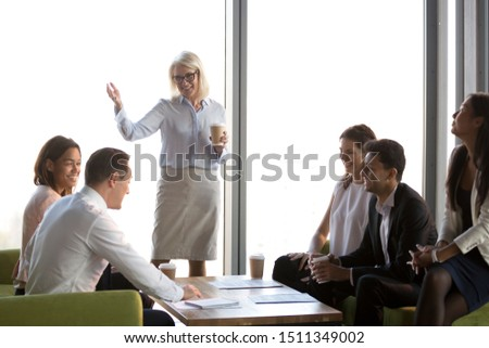 Smiling mature businesswoman holding briefing with diverse employees, team leader congratulating subordinate with business success, happy colleagues team building activity, corporate staff training