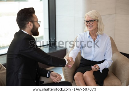 Smiling mature businesswoman shaking hand of business partner at meeting, greeting or making agreement, good deal, successful negotiations or job interview, hr manager and applicant handshaking