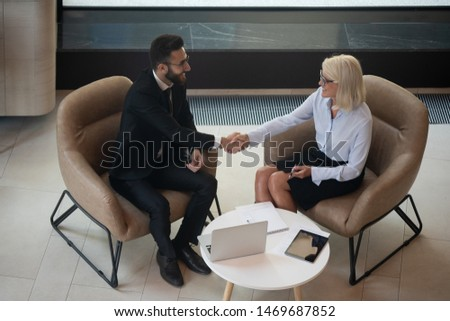 Smiling mature businesswoman shaking hand of business partner, greeting or making agreement, good deal, successful negotiations or job interview, hr manager and applicant handshaking top view