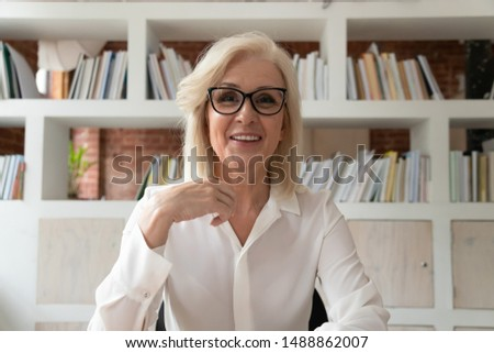 Smiling mature businesswoman sit at desk in office talk with client customer have conversation on webcam, happy positive middle-aged female employee in glasses video call at workplace