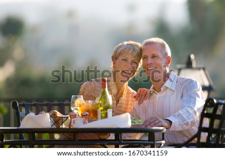 Smiling mature couple eating at outdoor restaurant table at camera