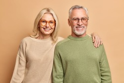 Smiling mature couple embrace look gladfully at camera pose for family portrait happy children came to visit them wear transparent glasses casual jumpers isolated over brown background. Age concept
