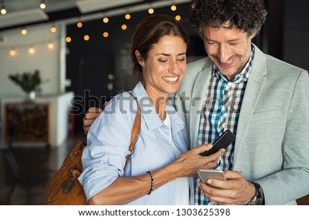 Smiling mature couple embracing while looking at smartphone. Couple sharing media on smart phones while standing in cafeteria. Happy man and beautiful woman using cellphone and laughing.