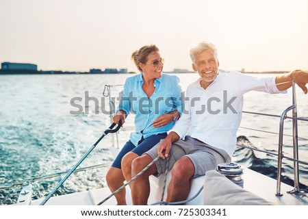 Smiling mature couple sitting together on the deck of their boat while out for a sail on a sunny afternoon