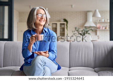 Smiling mature elder 60s woman sitting relaxing with cup of tea, coffee. Senior mid age stylish look woman with eyeglasses portrait with cup looking away at modern home.