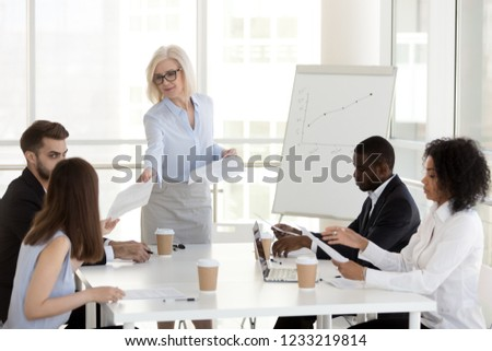 Smiling mature female manager company leader gives handout to diverse employees team at office group meeting, middle aged businesswoman handing paper finanical report to workers at corporate briefing