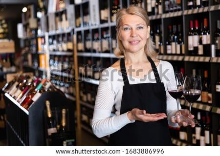 Smiling mature female vintner proposing degustation of wine in modern wine shop