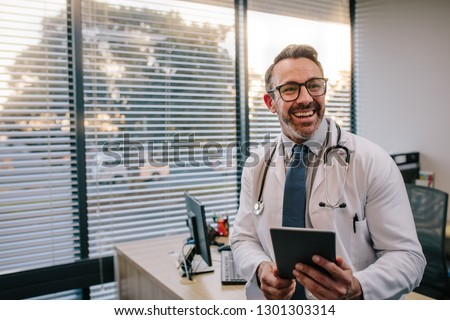 Smiling mature male doctor with digital tablet in his office. Friendly medical professional with tablet computer in clinic.