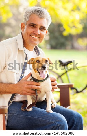 smiling mature man and pet dog outdoors