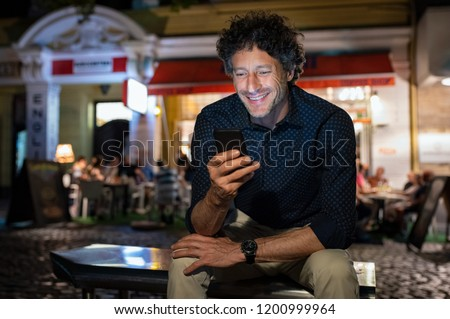 Smiling mature man checking phone while sitting on bench outside restaurant. Successful businessman reading message on mobile phone at night. Senior entrepreneur feeling happy on receiving mail.