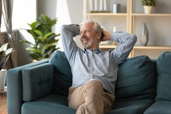 Smiling mature man dreaming, relaxing on cozy couch alone, happy older senior male with hands behind head sitting resting on sofa in living room, looking in window, thinking about good future