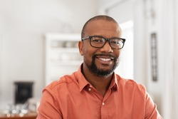Smiling mature man wearing spectacles looking at camera. Portrait of black confident man at home. Successful entrepreneur feeling satisfied.