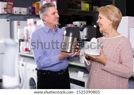 smiling mature married couple in shopping center buys small kitchen household appliances for their home