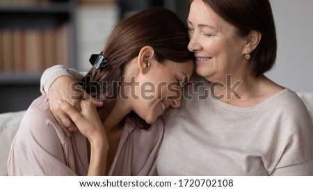 Smiling mature mother hugging adult daughter close up, expressing love and care, family enjoying tender moment, happy young woman and middle aged mum cuddling, two generations good relations