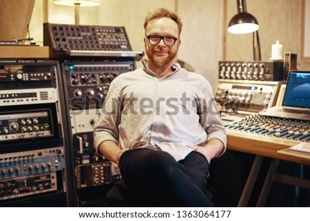 Smiling mature music producer sitting in a sound recording studio surrounded by various pieces of audio equipment #1363064177