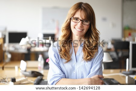 Smiling mature professional businesswoman in casual, with arms crossed standing in office. Shallow focus. Foto d'archivio ©