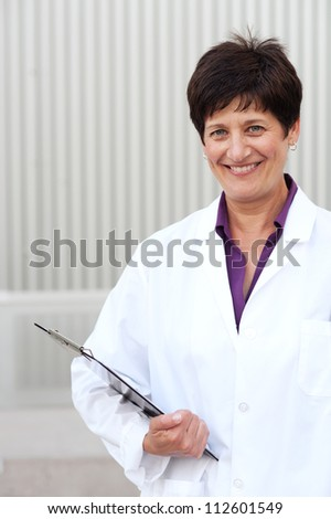 Smiling mature professional woman dressed in lab coat standing outside