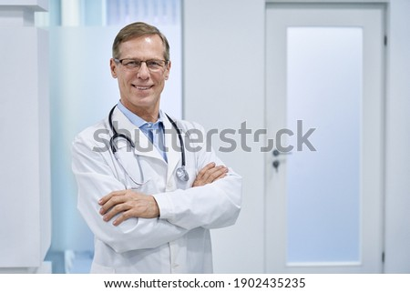 Smiling mature senior doctor wearing glasses, stethoscope and white lab medical coat standing in hospital looking at camera. Middle aged old 60s male physician, practitioner, cardiologist portrait. Photo stock ©