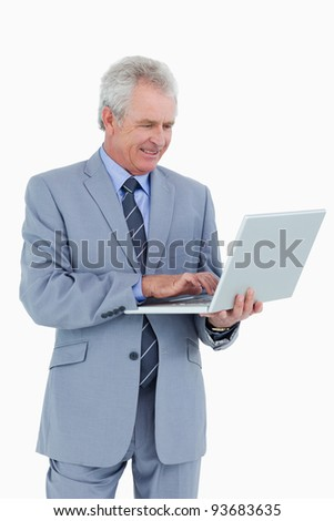 Smiling mature tradesman working on his laptop against a white background