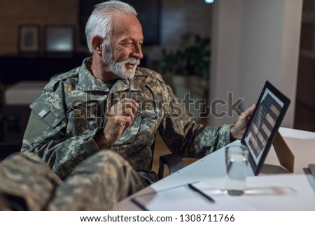 Smiling mature US military soldier looking at old American flag in picture frame and feeling nostalgic.