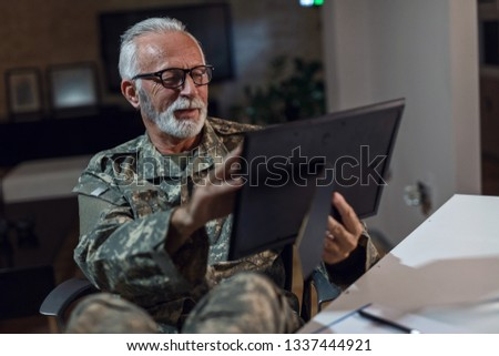 Smiling mature veteran sitting in his office and feeling nostalgic while looking at picture in photo frame.