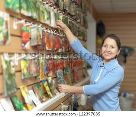 Smiling mature woman chooses packed seeds at store for gardener